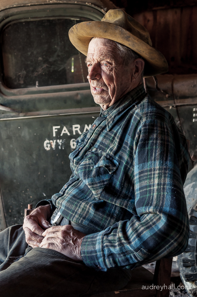 Montana rancher John Hoiland sits in his barn as artist Hugh Wilson paints a life portrait.